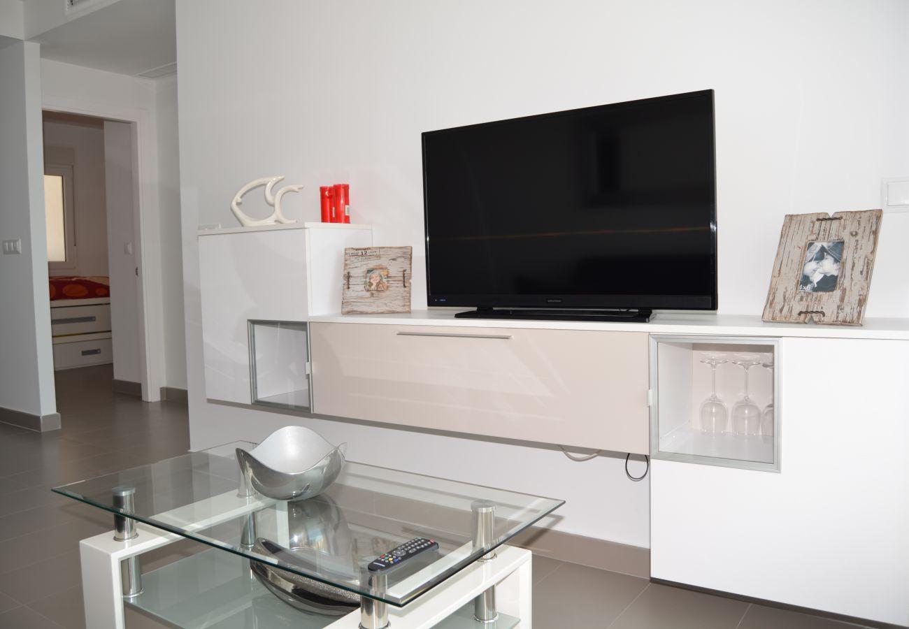 Salón moderno bien equipado con TV y buen mobiliario